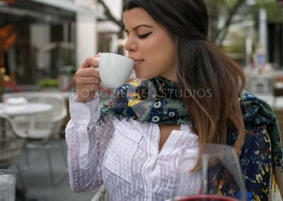 glamour model drinking cappuccino at outdoor restaurant