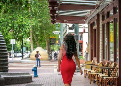 african american glamour model in red dress walking on sidewalk