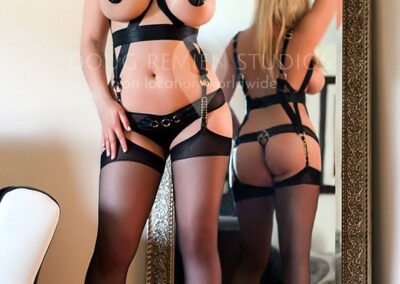 blonde glamour model in front of mirror in black bordelle lingerie and black stockings