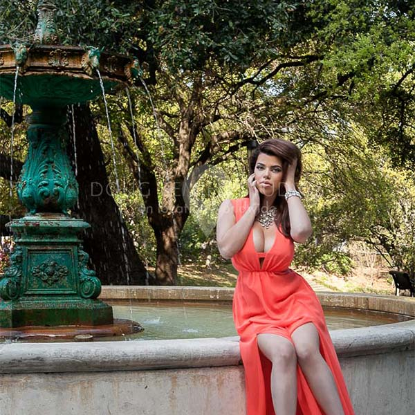 glamour model in dress by outdoor fountain