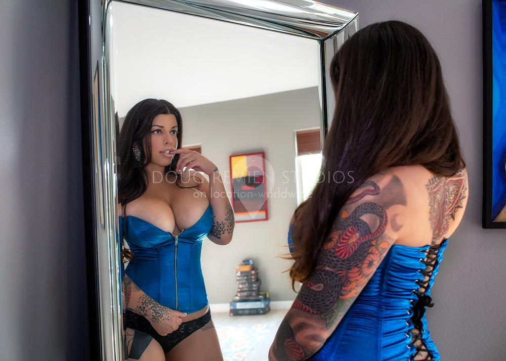 large breasted glamour model wearing blue corset in front of a mirror