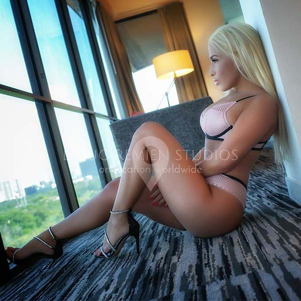 blonde glamour model in lingerie in hotel room with a view